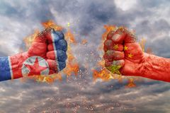 Two fist with the flag of North Korea and China faced at each other. Ready for fight Royalty Free Stock Images