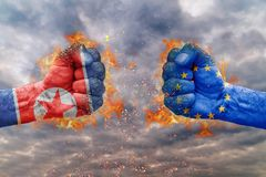 Two fist with the flag of North Korea and EU faced at each other. Ready for fight Stock Photos