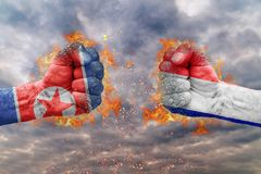 Two fist with the flag of North Korea and France faced at each other. Ready for fight Royalty Free Stock Photo