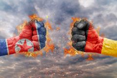 Two fist with the flag of North Korea and Germany faced at each other. Ready for fight Stock Photos