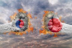Two fist with the flag of South Korea and Japan faced at each other. Ready for fight stock photo
