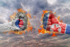 Two fist with the flag of South Korea and North Korea faced at each other. Ready for fight royalty free stock photo