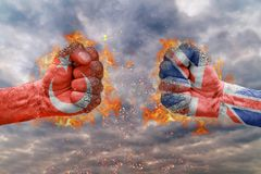 Two fist with the flag of Turkey and Great Britain faced at each other. Ready for fight stock photography