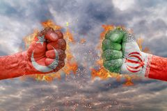 Two fist with the flag of Turkey and Iran faced at each other. Ready for fight stock photos