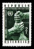 Two fists with spanner, UNO badge, I.L.O. International Labor Organisation, 50th Anniversary serie, circa 1969. MOSCOW, RUSSIA - AUGUST 18, 2018: A stamp printed stock photography