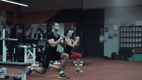 Two fit athletes doing cardiovascular exercises. Two fit young athletes doing cardiovascular exercises in a darkened gym in a running motion with raised hands as stock footage