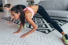 Two fit girls doing home workout performing lateral lunges at home. Two fit girls doing home workout performing lateral lunges at home royalty free stock images