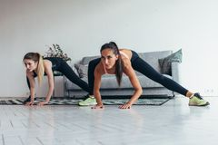 Two fit girls doing home workout performing lateral lunges at home. royalty free stock photos