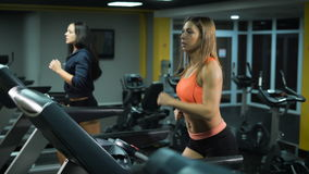Two fit girls running at the gym. Two friends run on the treadmills together to burn calories and to develop endurance stock video