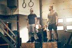 Two fit men standing on boxes during a workout session. Two fit men standing on boxes during a gym workout session with friends watching in the background stock photography