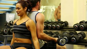 Two fit people lifting dumbbells. Sitting in gymnasium stock footage