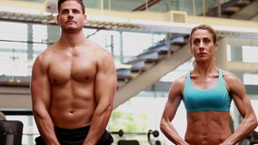 Two fit people lifting kettle bells together stock video footage