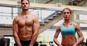 Two fit people lifting kettle bells together. At the gym stock video