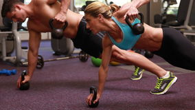 Two fit people lifting kettle bells together in plank position