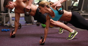 Two fit people lifting kettle bells together in plank position. At the gym stock footage