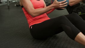 Two fit people squatting with medicine balls. In crossfit stock video footage
