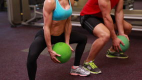 Two fit people squatting with medicine balls stock video footage