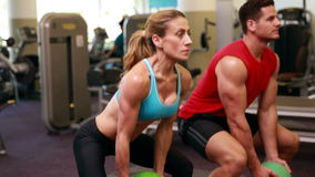 Two fit people squatting with medicine balls stock footage