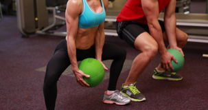 Two fit people squatting with medicine balls stock video