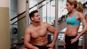 Two fit people taking a break and chatting together. At the gym stock video