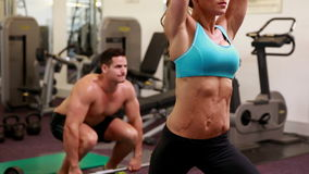 Two fit people working out at crossfit session. At the gym stock video footage