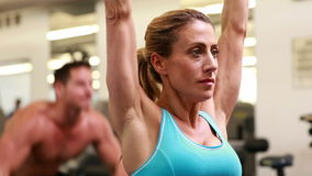 Two fit people working out at crossfit session. At the gym stock footage
