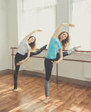 Two fit pretty women are doing ballet exercise Stock Photography