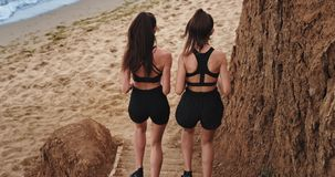 The two fit and sporty girls run to the beach and enjoy each other s company while doing sport. Slow stock video