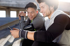 Two fit and sporty youn men using mobile phone in the city. Royalty Free Stock Image