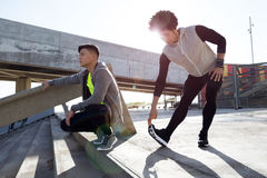 Two fit and sporty young men relaxing and stretching after work Stock Photo