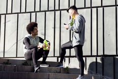 Two fit and sporty young men relaxing and stretching after work Stock Photos