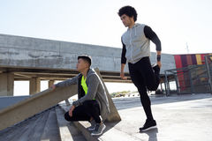 Two fit and sporty young men relaxing and stretching after work Stock Photography