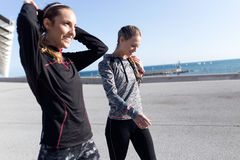 Two fit and sporty young women relaxing after work out in the pa Stock Images