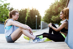 Two fit and sporty young women relaxing after work out in the park. Portrait of two fit and sporty young women relaxing after work out in the park Stock Images