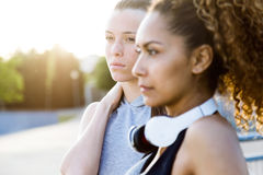 Two fit and sporty young women relaxing after work out in the park. Portrait of two fit and sporty young women relaxing after work out in the park Royalty Free Stock Image