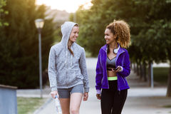 Two fit and sporty young women relaxing after work out in the park. Portrait of two fit and sporty young women relaxing after work out in the park Royalty Free Stock Photography