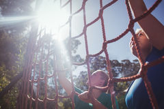 Two fit women climbing a net during obstacle course training. In the boot camp royalty free stock image