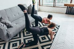 Two fit women doing bent knee donkey kick exercise in all fours position working out their buttocks at home royalty free stock photos