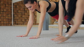 Two fit women doing exercises lying inside fitness studio. Sport instructors training push ups from hands to elbows. Attractive sportswoman with picked hair in stock video