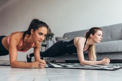 Two fit women doing plank exercise on floor at home Training back and press muscles, sport, fitness workout Royalty Free Stock Image