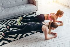 Two fit women doing plank exercise on floor at home Training back and press muscles, sport, fitness workout.  royalty free stock photography