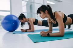 Two fit women doing planks exercise at gym. Two girls making effort while doing planks during workout in gym. Female friends doing push ups exercise at fitness Royalty Free Stock Images