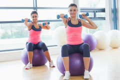Two fit women exercising with dumbbells on fitness balls Royalty Free Stock Photography