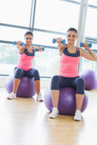 Two fit women exercising with dumbbells on fitness balls Royalty Free Stock Images