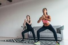 Two fit women exercising together doing squats at home royalty free stock images