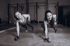 Two fit women in gym doing fitness exercises with dumbbells staying in plank pose, black and white royalty free stock photography