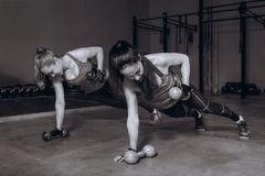 Two fit women in gym doing fitness exercises with dumbbells staying in plank pose, black and white stock images