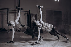 Two fit women in gym doing fitness exercises with dumbbells staying in plank pose, black and white royalty free stock photo
