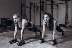 Two fit women in gym doing fitness exercises with dumbbells staying in plank pose, black and white stock image