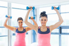 Two fit women lifting dumbbell weights in gym Stock Photos